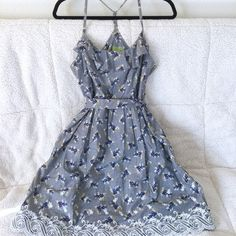 ✨BOGO✨Floral Gray Sundress with Waist Tie Super cute gray sundress with blue, white, and pink flowers. Narrow halter straps and front fluttering lapel along neckline. Lace design along bottom hem. The waist tie can be tied in the back or front (back in picture), and the band is actually twice the width of pictured. I preferred a thinner band size, but I have also spread it out to make a gigantic Disney princess-like bow. The skirt of the dress is pleated at the waist so it flutters out…
