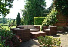 плетеная наружная мебель заставляет сад привлечь Вас, чтобы сидеть и расслабиться
