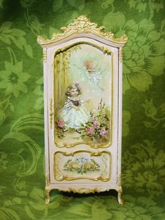 Part of the Finding Fairies Collection in a soft pink. Original, hand-painted fairytale art on a miniature cupboard with dancing fairies, rabbits, roses and forget-me-nots. Approx. 7 tall NOTE: Made to order. Please allow approx. 10 to 12 weeks for shipping from purchase or final payment. May be