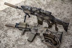On the ground is a SCAR-L. On the bipod is a SCAR-H. The SCAR-L has a one-point sling. Both have suppressors.