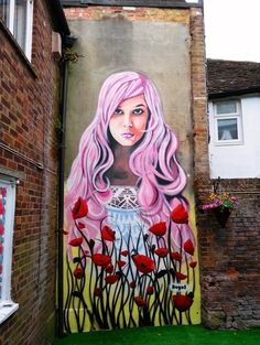 This mural is painted in the garden of a coffee shop in Sittingbourne High Street. The client wanted something bright and flowery, so we painted this pink haired girl surrounded by poppies.