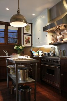 GREEN with envy over this range & hood, love the cabinets and the wooden countertops as well.  Tiny but very functional