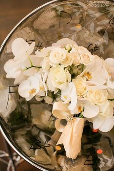 Anna and Spencer Photography , Atlanta wedding photographers . White phalaenopsis orchid and rose bridal bouquet on a steel drum instrument . Flowers by Edge Design Group in Atlanta .