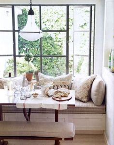 cozy kitchen banquette.  natural linens, black iron windows, and antique pendant lighting. by cristina