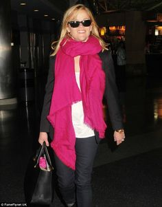 In the pink: Reese wore a bright pink scarf to jazz up a monochrome outfit and sported a pair of Ray Ban sunglasses for her flight