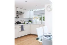 Modern white kitchen with wood floors and blue flowers on glass table - Home and Garden Design Idea's