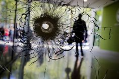 The image is strangely beautiful, but the thing that caused it is not. A bullet hole pierces a shop window on the Champs-Élysées in Paris on April 21, the day after a gunman opened fire on the city's most famous boulevard, killing a police officer.