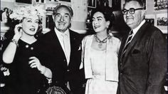 """Bette Davis, Jack Warner, Joan Crawford and Robert Aldrich pose for reporters and photographers in """"the trophy room"""" on the Warner Bros. Studios lot in Los Angeles on July 18,"""