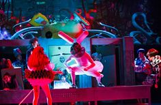 Ms Manxome (Anna Francolini) urges her corrupted Alice (Carly Bawden) to kill the White Rabbit (Joshua Lacey) that she followed as the horrified Company look on in Wonder.land at the National Theatre.