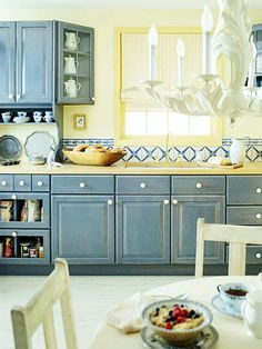 blue and yellow kitchen. Love the one glass front cabinet door.