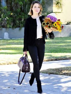 Sophia Bush wears a suede fringe jacket with a white t-shirt, black skinny jeans and black suede ankle boots.