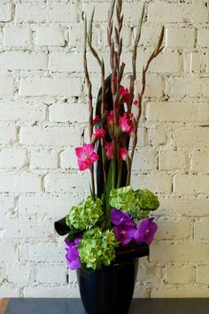 A bright and colourful arrangement for one of our corporate clients, including green hydrangea, purple vanda orchids, cerise gladioli and black-tie leaves. #reidsflorists #corporateflowers