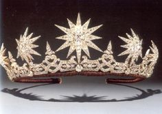 A tiara in the form of five stars supported on a gallery of stylized foliage. A highly succesful tiara type, these jewels invite comparison between starshine & the scintillation of the diamond. The inclusion of stars may also allude to Shakespeare's Sonnet 116, in which he describes love as 'the star to every wandering bark'.