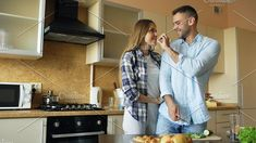 Happy young couple in the kitchen. Handsome man meet and feed his girlfriend early morning. Romantic