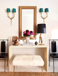 a dream vanity - perfectly style with brass accents, a chic sheepskin stool, and oversized mirror.