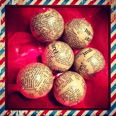 Home made christmas baubles , made with polystyrene balls & vintage style paper finished with a red ribbon to hang with