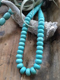 """Turquoise oval beads. Each strand is unique and perfect for display. Approx. 27"""" long Beads measure approx. .5"""" dia. Shown with oblong turquoise beads"""