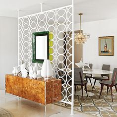 """From March 2012 Coastal Loving Johnathan Adler design - Palm Beach apartment.  Perhaps a little too retro (or as they say """"eclectic"""" and """"hip""""), but I like the black & white upholstery on the chairs, the mix and match w/ white table and stained chairts, and the refinished buffet.  The boy in the dunce cap on the wall is scary."""