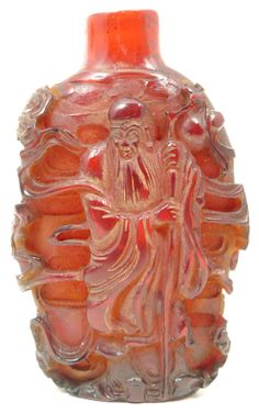 """CHINESE CARVED RED AMBER SHOU XING SNUFF BOTTLE ~ Chinese hand carved amber snuff bottle with relief design depicting Shou Xing, maiden and attendant. Measures 2 3/8"""" height (2.9cm). Total weight of 34 grams."""