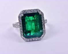 An 18k white gold ring with a 6.88ct emerald center stone, surrounded by 0.58 round diamonds.