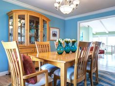 Turquoise walls provide a soothing backdrop in this traditional dining room.