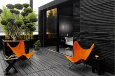 The combination of a monochrome palette with orange furniture works really well.
