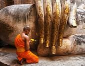 Buddhist monk in front of the seated buddha at Wat Si Chum, Thailand