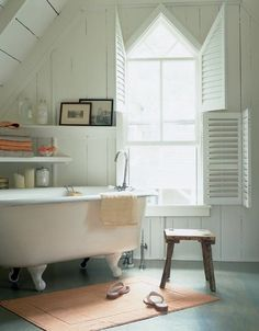 love white painted panelling, pointed window, eaves, bathtub in corner with art