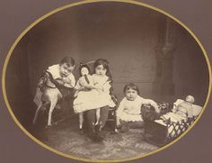 Unusually large format albumen print showing three children with toys almost as large as they are, including two large dolls and a rocking horse, by an unidentified American photographer circa 1870