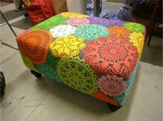 Adhere colorful crocheted doilies to a solid fabric lined ottoman.