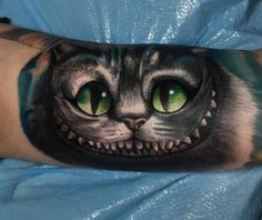 Realistic Chesire cat tattoo on the left inner arm.