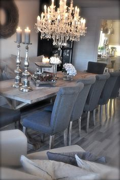 elegant dining with slipper chairs in light grey blue, clean lines, and crystal chandelier