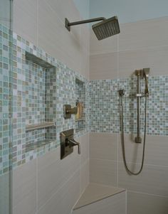 I like this wide band of small glass tiles; adds a nice touch to this otherwise plain jane shower. via House of Turquoise