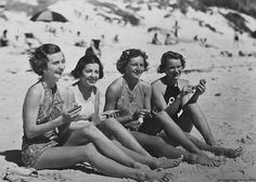 Four 1930s bathing beauties getting ready to powder their noses at the beach.
