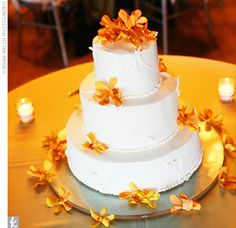 Alexis and Phil's three-tiered round cake was adorned with white buttercream frosting featuring a vine pattern and topped with whimsical sienna-hued Mokara orchids. Two layers were chocolate with mocha ganache, while the remaining one was carrot cake.