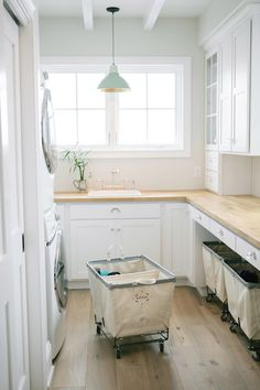 Gorgeous laundry room boasts white shaker front cabinets and light butcher block counters. A stackable white front loading washer and dryer peek out from beside the closet door