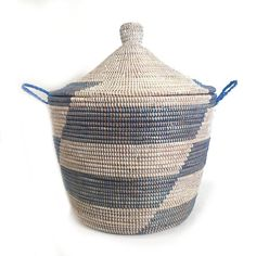 "• Hand woven in Senegal• Millet grass and recycled plastic• 24""h with lid, 14""h without• 19"" diameter This African basket features an alternating blue stripe that can add a pop of color to any room. Large enough to be storage solution for towels or laundry, and stylish enough to be a focal point to any space. For more than 20 years, the ethical brand Mbare (pronounced ""im-bah-ree"") has worked with artisans all across Africa to create stunning baskets and glassware. Mbare's gorgeous baskets… Large Storage Baskets, Decorative Storage, Basket Weaving, Hand Weaving, Laundry Basket With Lid, Large Woven Basket, Hamper Basket, Dyi Crafts, Weaving Techniques"
