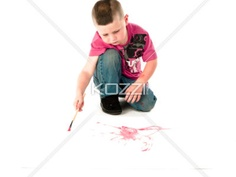 young aspiring painter - Small boy doing brush strokes on a white cardboard.