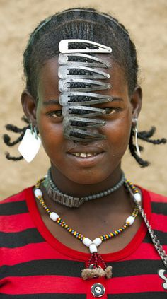 In southern Ethiopia deep within the Omo Valley you'll find the semi-nomadic tribe known as 'The Daasanach'. The fashion right now is for hairclips and watchstraps, but sometimes just hairclips . Photography Eric Lafforgue