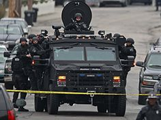 """Police arrive on an armored police vehicle as they surround an apartment building. The suspects were identified to The Associated Press as coming from the Russian region near Chechnya, which has been plagued by an Islamic insurgency stemming from separatist wars. A law enforcement intelligence bulletin obtained by the AP identified the surviving bomb suspect as Dzhokhar A. Tsarnaev, a 19-year-old who had been living in Cambridge, just outside Boston, and said he """"may be armed and dangerous."""""""