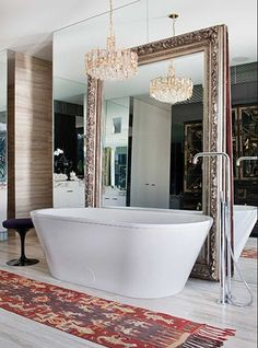 great mix - modern tub, opulent chandelier and mirror frame and kilim rug