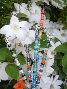 Bracelet beads (sold in bulk)..threaded rods,nuts,pretty drawer pulls...there you have it..put a nut on the bottom so the beads dont fall off , leaving room for sticking into the ground (take into account the weight of the beads)..slide on beads,top with a drawer pull..voila!! Pretty garden stakes..