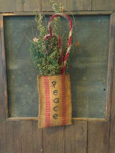 Prim Handid' Christmas Pocket...in grunged burlap strapping & stuffed with canes.