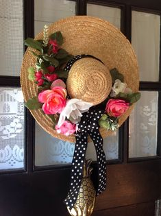I decorated this straw hat for my front door with flowers and ribbon bought at AC Moore.