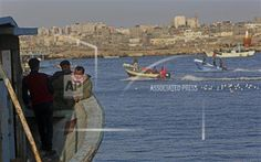 Palestinian fishermen have a small talk on their boat while waiting to sail out on the waters of the Mediterranean Sea at the fisherman's port in Gaza City, northern Gaza Strip, Saturday, Feb. 14, 2015. (AP Photo/Adel Hana)