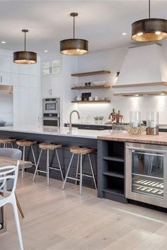 Modern Farmhouse Kitchen Design, Island with Beverage Centre Modern Farmhouse, Trickle Creek Designer Homes, Trickle Creek Custom Homes, modern farmhouse kitchen design ideas, modern farmhouse kitchen design inspiration, blue cabinets, white cabinets, white shaker cabinets, blue shaker cabinetry, open concept kitchen and dining room, butcher block island countertop, marble counter tops dark cabinets, island with beverage cooler, kitchen island with beverage fridge, kitchen island with bar…