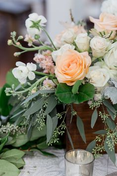 detail of wedding centerpiece in a varnished wood box highlighted by peach roses, white ranunculus, peach stock, white majolik spray roses, seeded eucalyptus, dusty miller and lemon leaf.