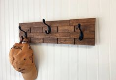 This rustic wood coat rack is perfect in your entryway as a coat hanger, or in your bathroom as a towel rack. This rack is stained Early American and fully sealed. It is wall mounted, and has 3 heavy duty coat hooks. This handmade rustic coat rack has a lot of interesting details since it is made from 18 individual pieces of wood. Each piece of wood has its own color, grain pattern and markings making each coat rack completely unique. The rack is fully sealed to protect the wood for many…