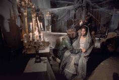 Full shot of Roger Davis as Jeff Clark kneeling next to Kathryn Leigh Scott as Maggie Evans in dark room filled with cobwebs, dust and candles. House of Dark Shadows movie