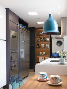 As paredes da cozinha exibem o mesmo laminado dos armários. Bancada de Silestone e piso da Portobello. Cadeira da A Lot Of e pendente da Bertolucci.